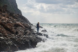 Woman tourist climbing on rocks at