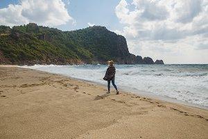 Woman tourist walking at coastline