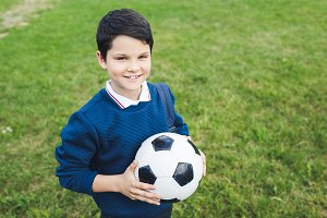 happy kid holding soccer ball and lo