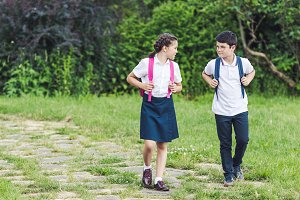 adorable schoolchildren walking by p