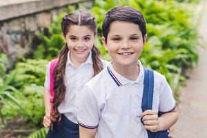 adorable schoolchildren with backpac
