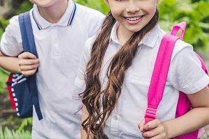 schoolchildren with backpacks lookin