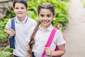 smiling schoolchildren with backpack