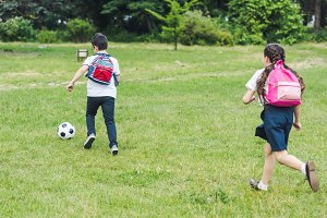 schoolchildren playing soccer togeth