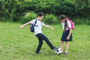 happy schoolchildren playing soccer