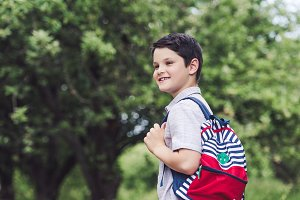 happy schoolboy with backpack lookin
