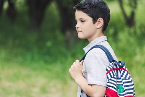thoughtful schoolboy with backpack l
