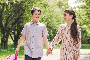 smiling kids holding hands and walki