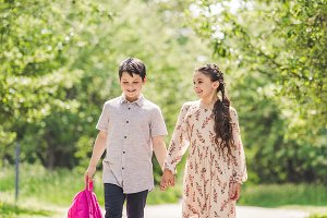 adorable kids holding hands and walk