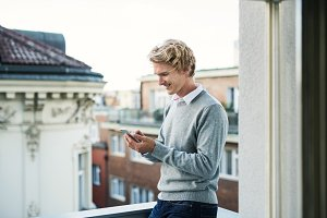 Young man with smartphone standing