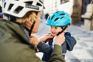 A young father putting on a helmet