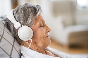 Sick senior woman with headphones