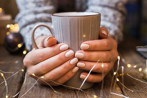 Female hands holding a cup. New Year