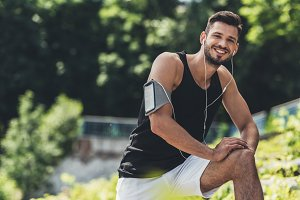 smiling sportsman in earphones with