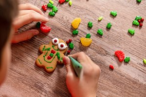 child decorates gingerbread cookie