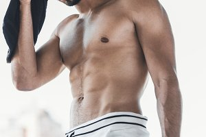tired shirtless male athlete wiping