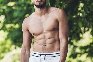 muscular shirtless young man looking