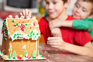children decorate gingerbread house