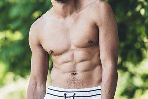 happy shirtless young man looking at