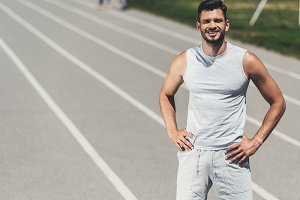 smiling young sporty man standing on