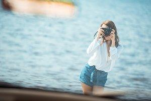girl taking photo of car near the se