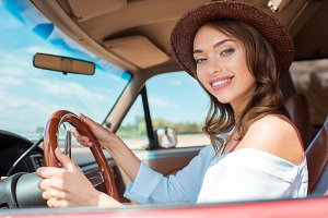 attractive smiling woman in hat driv