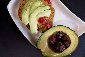 Toast with avocado and red fruits