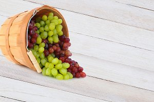 Basket of Grapes Spill on Wood Table