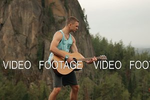 A man playing guitar standing on top