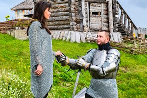 A knight in armor knelt before his