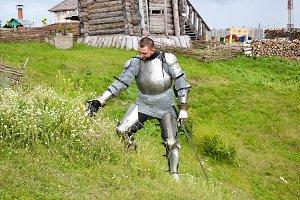 A knight in armor tears daisy