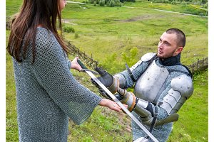 A lady in a chain mail hands a sword