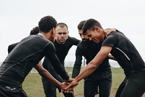 Football players in a huddle holding