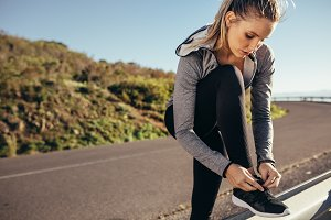 Woman runner tying her shoelace