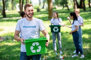 male smiling volunteer holding recyc