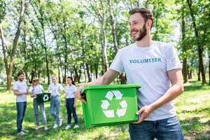 young male volunteer holding recycli