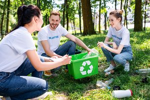 young smiling volunteers with green