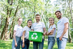 young happy volunteers with green re