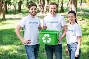 young volunteers with green recyclin