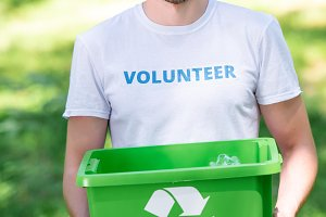 smiling male volunteer holding recyc