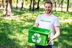 smiling volunteer holding recycling