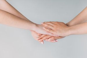 partial view of women holding hands,