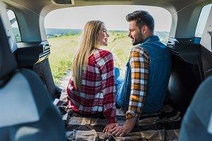 stylish young couple sitting on car