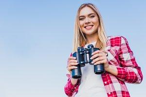 smiling female traveler holding bino