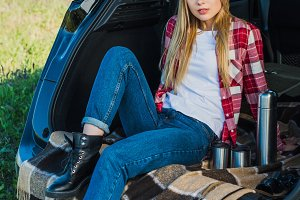 young woman sitting on car trunk wit