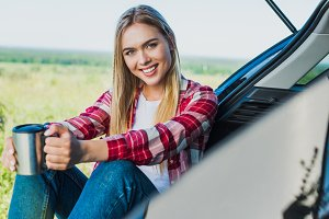 smiling young woman sitting on car t