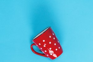 empty red ceramic mug in a white cir