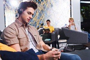 young businessman in headphones usin