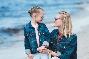 stylish mother and smiling daughter