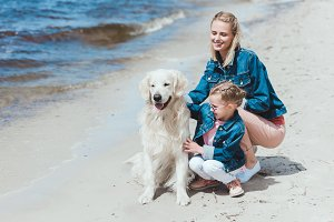 family sitting with golden retriever